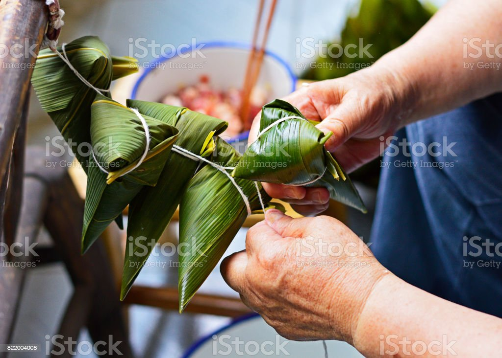 Two Hands Tighten String Over the Leaf to Make Zongzi stock photo