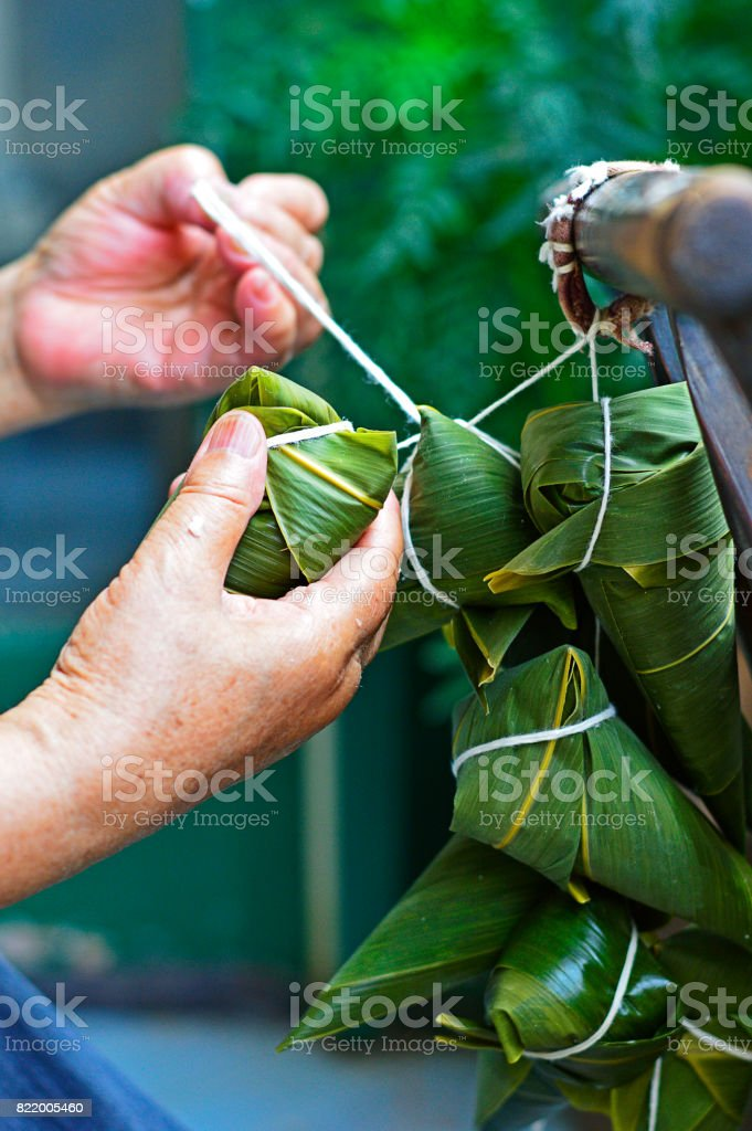 Two Hands Tighten the String to Make Zongzi stock photo
