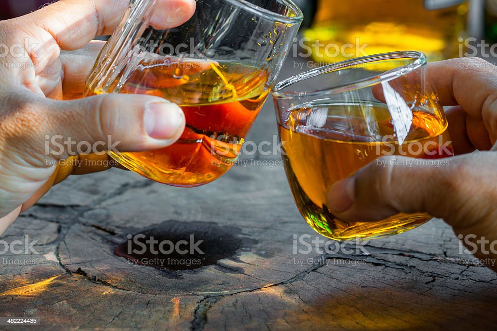Two hands toasting with plain whiskey over a rock surface stock photo