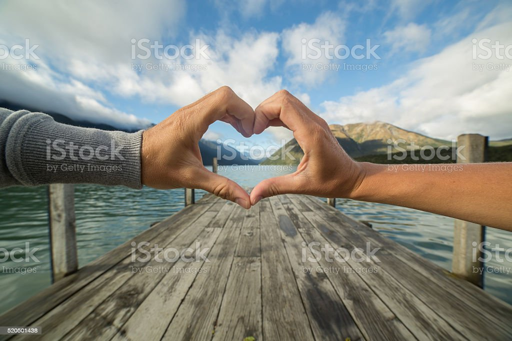 Two hands touching forms heart shape finger frame stock photo