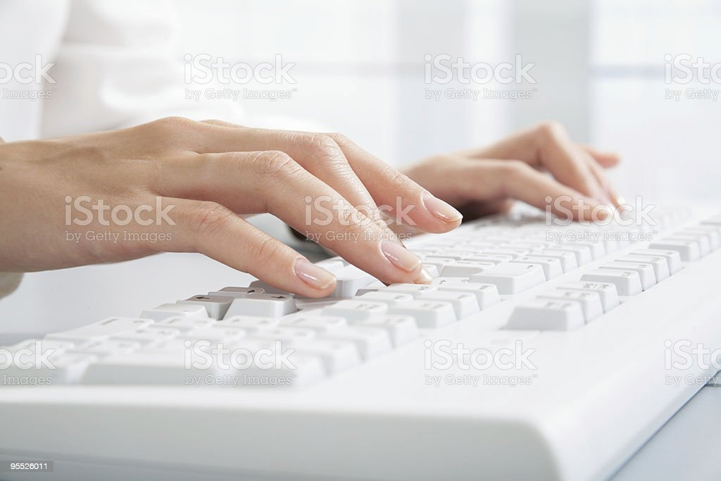 Two hands typing on a white computer keyboard royalty-free stock photo