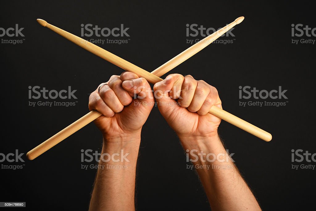 Two hands with crossed drumsticks over black royalty-free stock photo