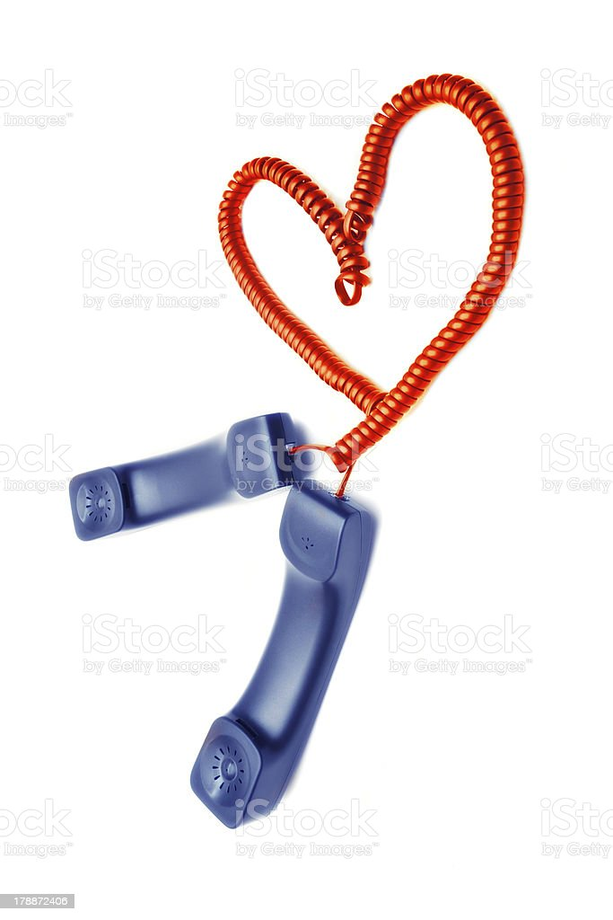 Two handsets with wires woven into a heart-shaped royalty-free stock photo