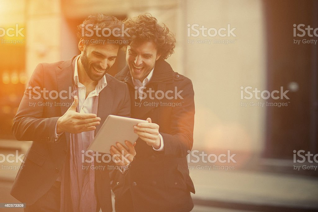 Two handsome guys watching on a digital tablet stock photo