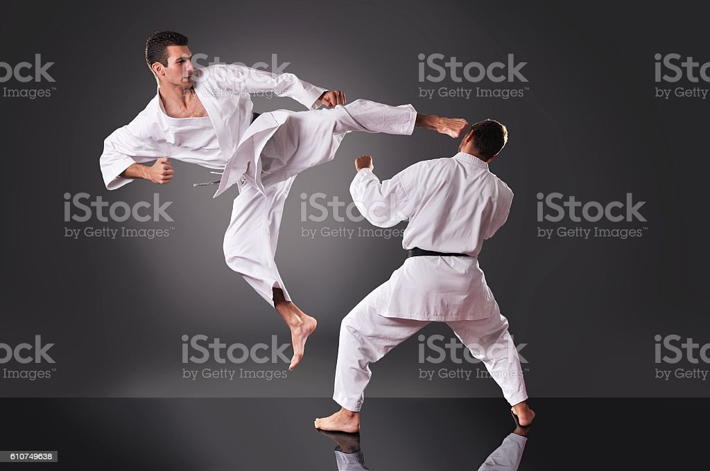 Two handsome young male karate fighting on the gray background stock photo