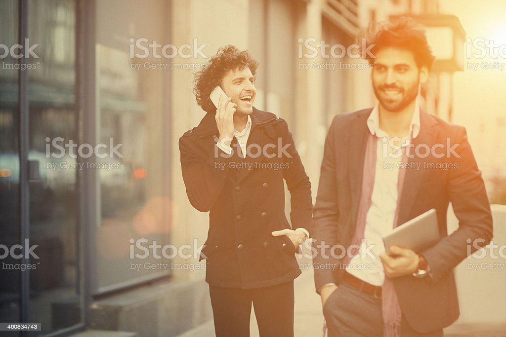 Two handsome young men walking on city street stock photo