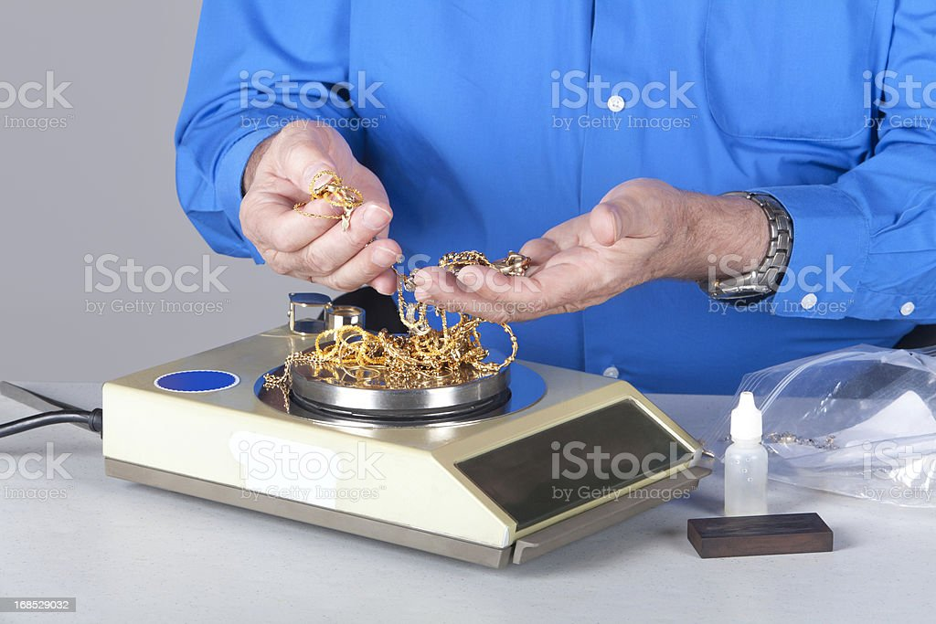 Two handy holding and weighing scrap gold stock photo