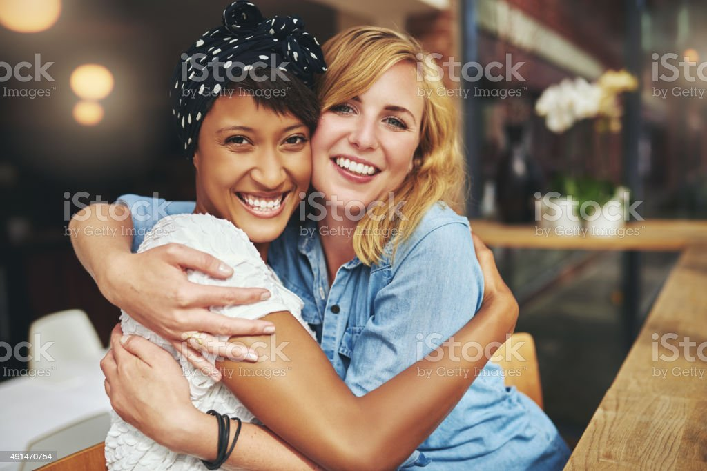 Two happy affectionate young woman hugging stock photo