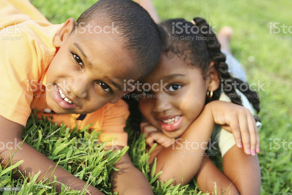 Two happy African American siblings laying in grass royalty-free stock photo
