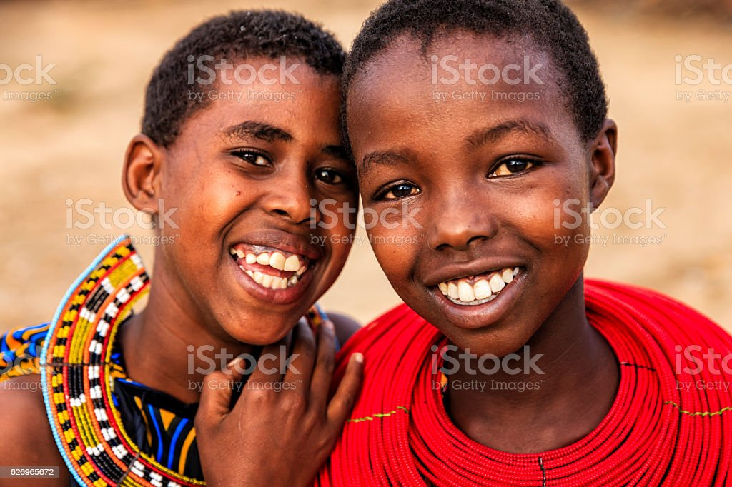 Two happy African young girls on savanna, East Africa stock photo
