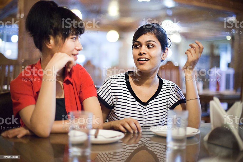Two happy Asian girls sitting in restaurant. stock photo