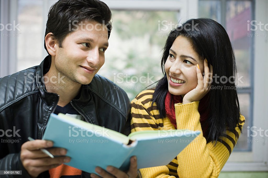 Two happy Asian, teenage, student friends reading book near window. stock photo