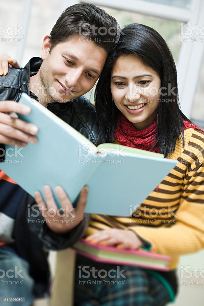 Two happy Asian, teenage, student friends reading book together. stock photo