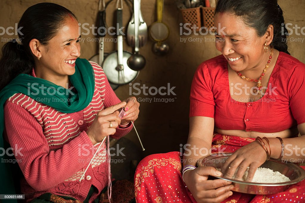 Two happy Asian village women in their traditional adobe kitchen. stock photo