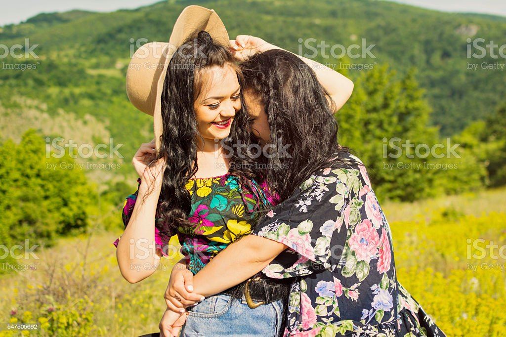 Two happy boho sisters hugging and laughing stock photo