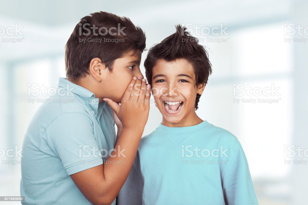 Two happy boys gossiping in the classroom stock photo