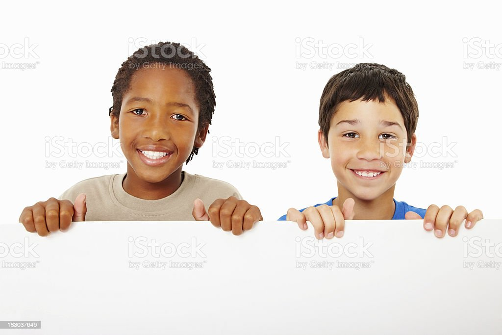 Two happy boys holding a white board royalty-free stock photo
