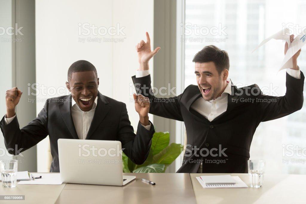 Two happy businessmen raising hands near laptop, celebrating success victory stock photo