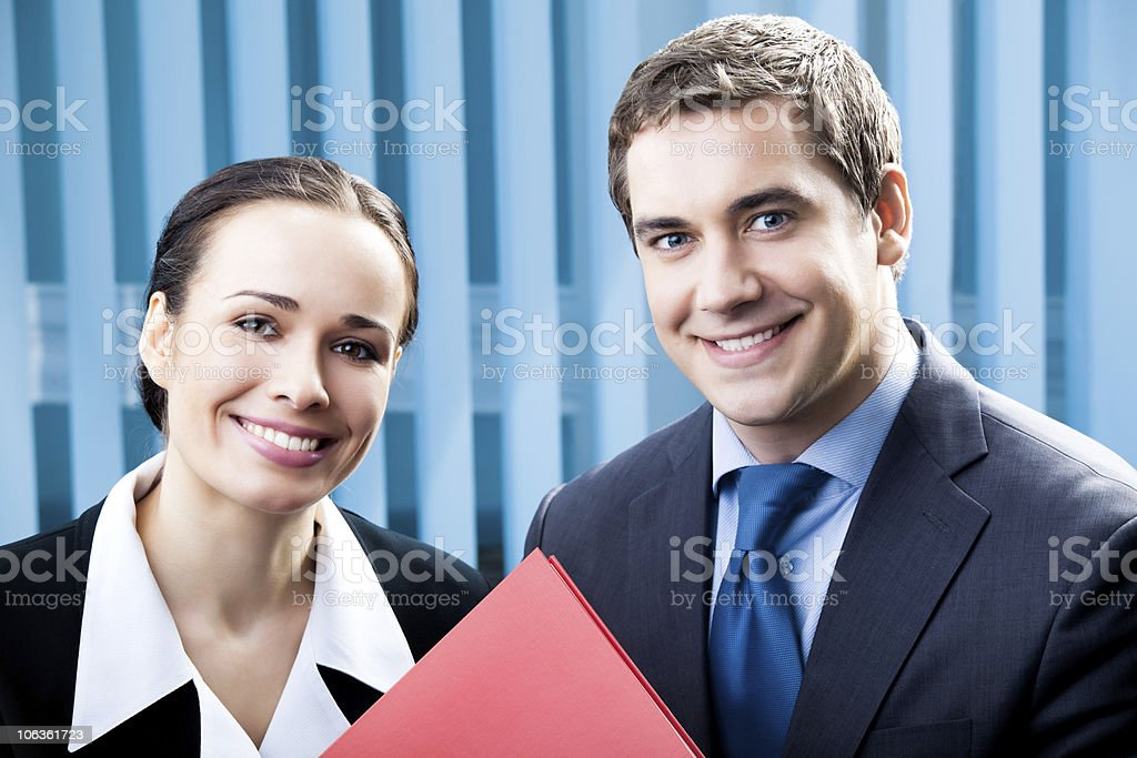 Two happy businesspeople with folder at office royalty-free stock photo