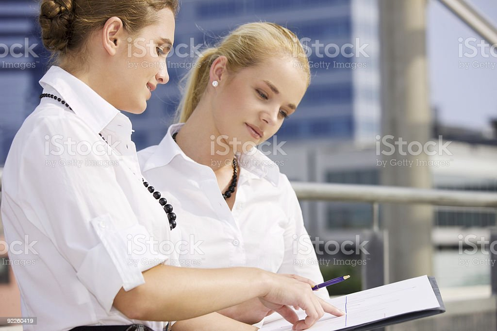 two happy businesswomen with paper chart royalty-free stock photo