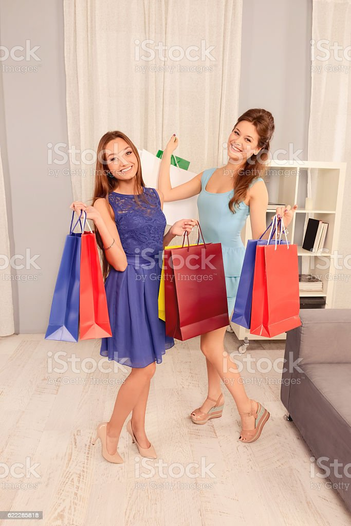 Two happy cheerful girls demonstrating their purchases stock photo