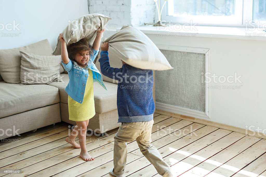 Two happy children is fighting a pillows each other stock photo