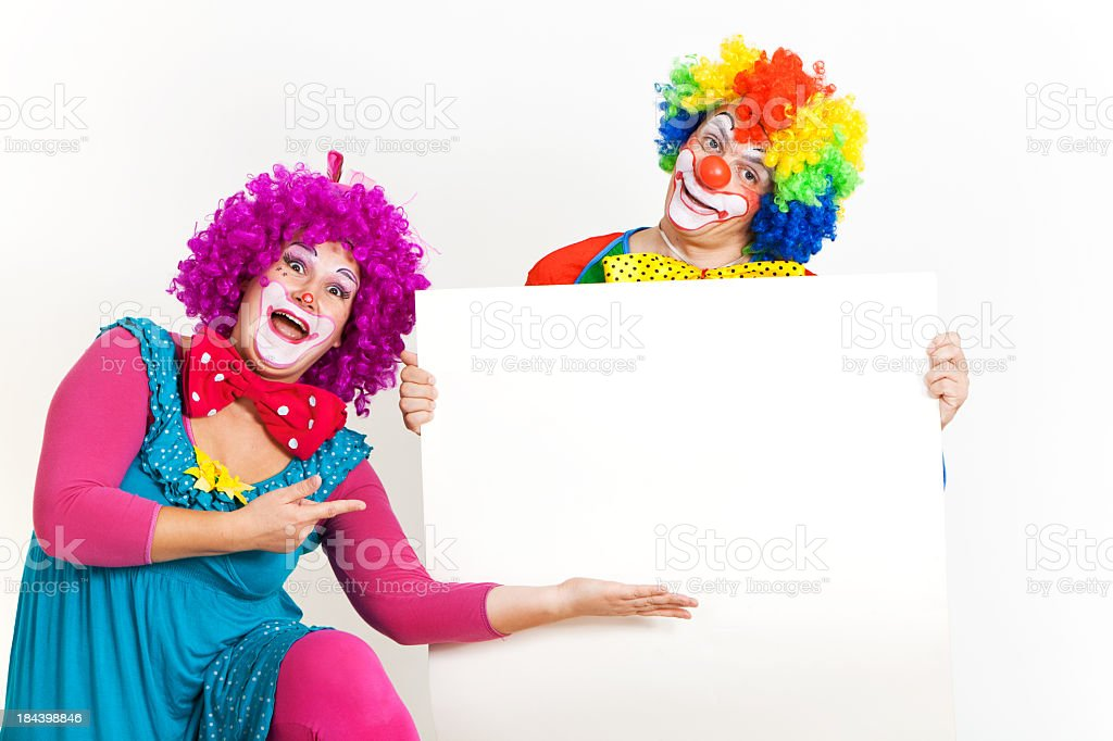 Two happy clowns holding blank banner with copy space royalty-free stock photo