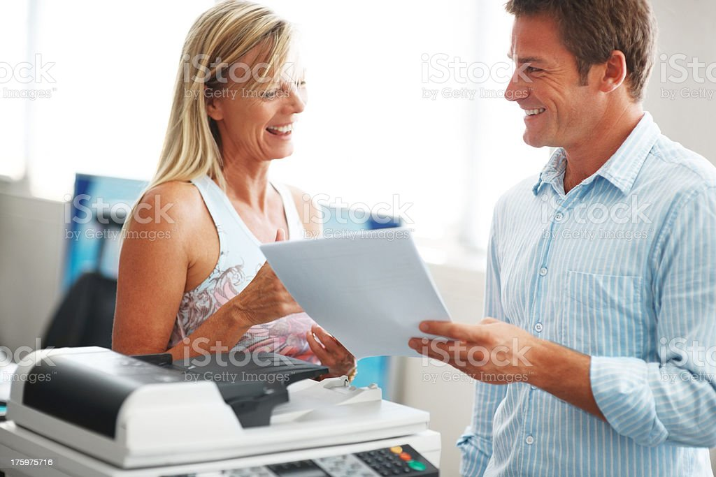 Two happy colleagues having a friendly chat in office stock photo