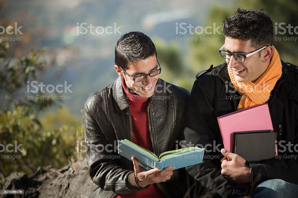 Two happy college students reading book together in mountain area. stock photo
