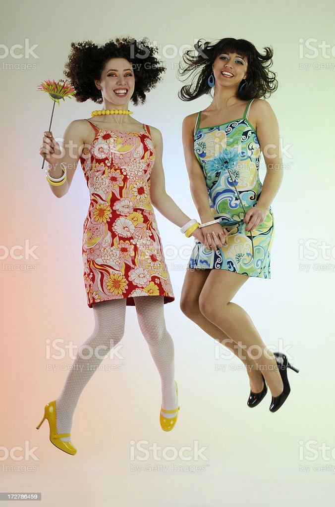 Two Happy Colorful Retro Style Girls Smiling, Jumping, Spring Flower royalty-free stock photo