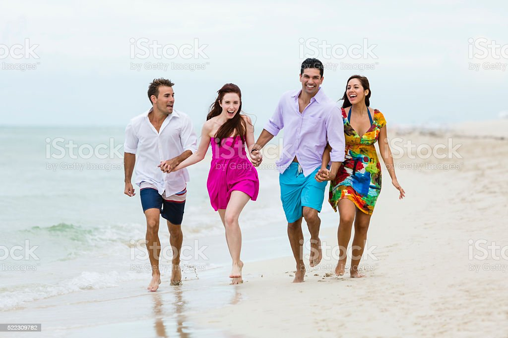 Two happy couple running together on the beach holding hands stock photo