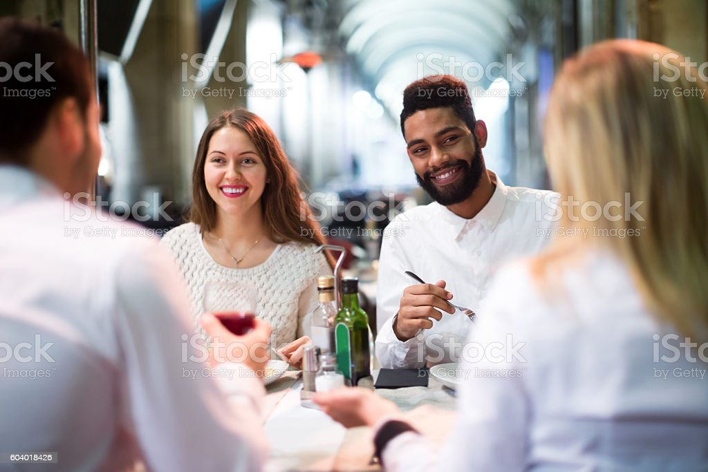 Two happy couples sitting at outdoor restaurant stock photo