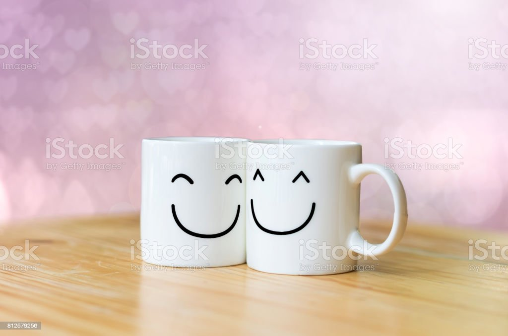 Two happy cups on wood table with Valentine's day hearts bokeh background stock photo