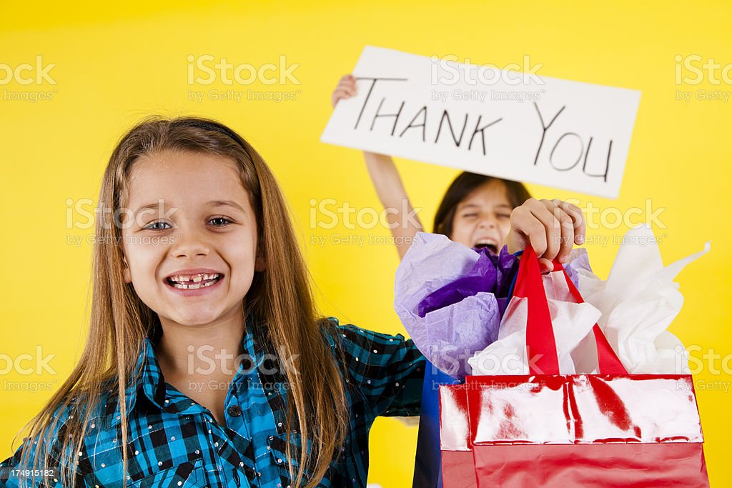 Two happy elementary age girls shopping holding thank you sign royalty-free stock photo