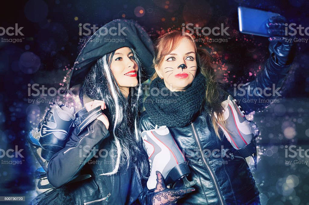 Two happy fancy dressed girls make selfie on mobile phone stock photo