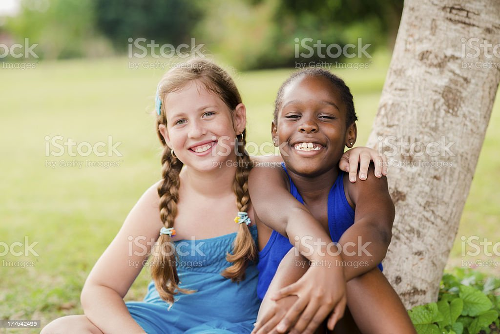 Two happy female friends hugging and looking at camera stock photo