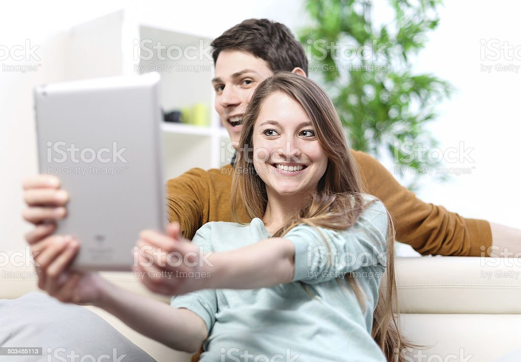 Two happy friends taking photo with tablet pc at home royalty-free stock photo