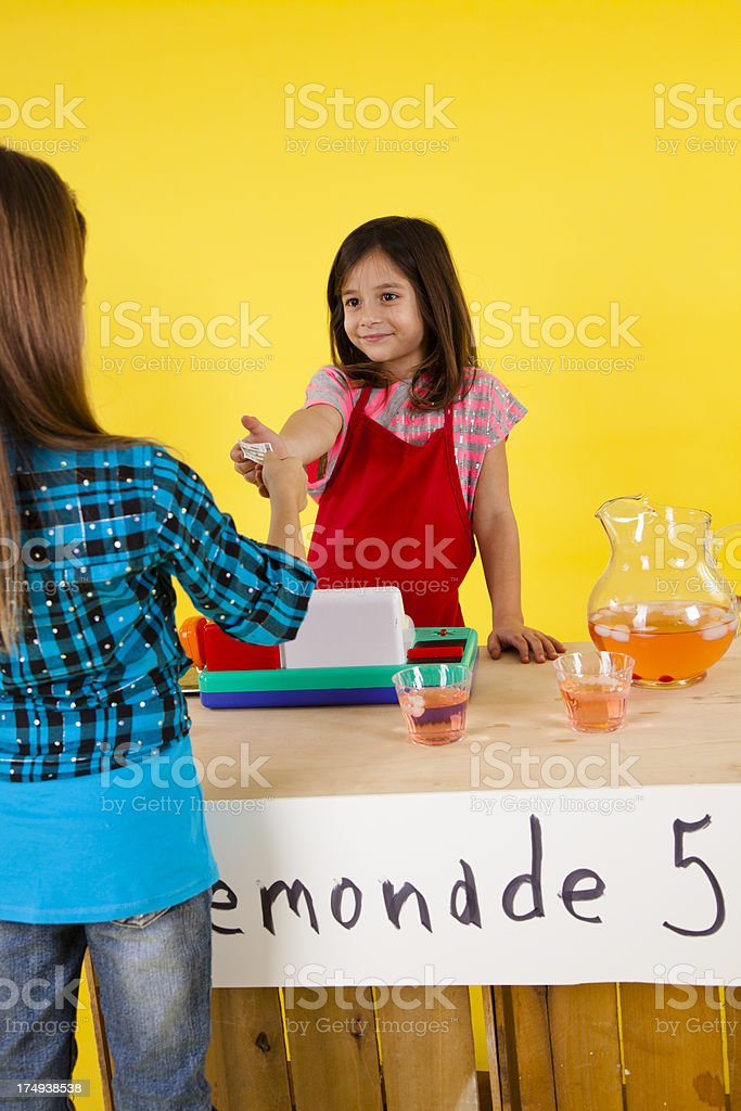 Two happy girls 7-8, one selling lemonade at a stand royalty-free stock photo