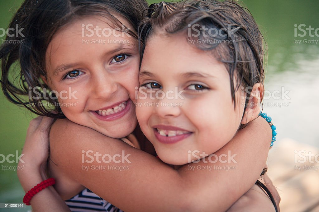 Two happy girls hugging stock photo