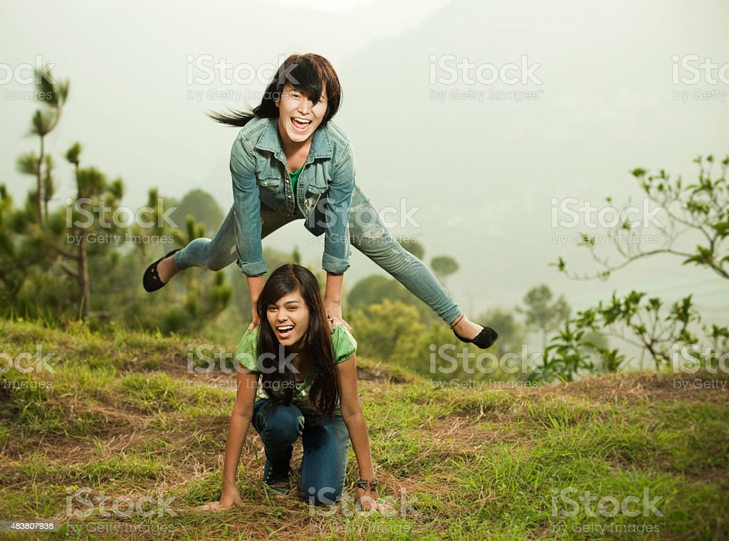 Two happy girls of different ethnicity playing leapfrog in nature. stock photo