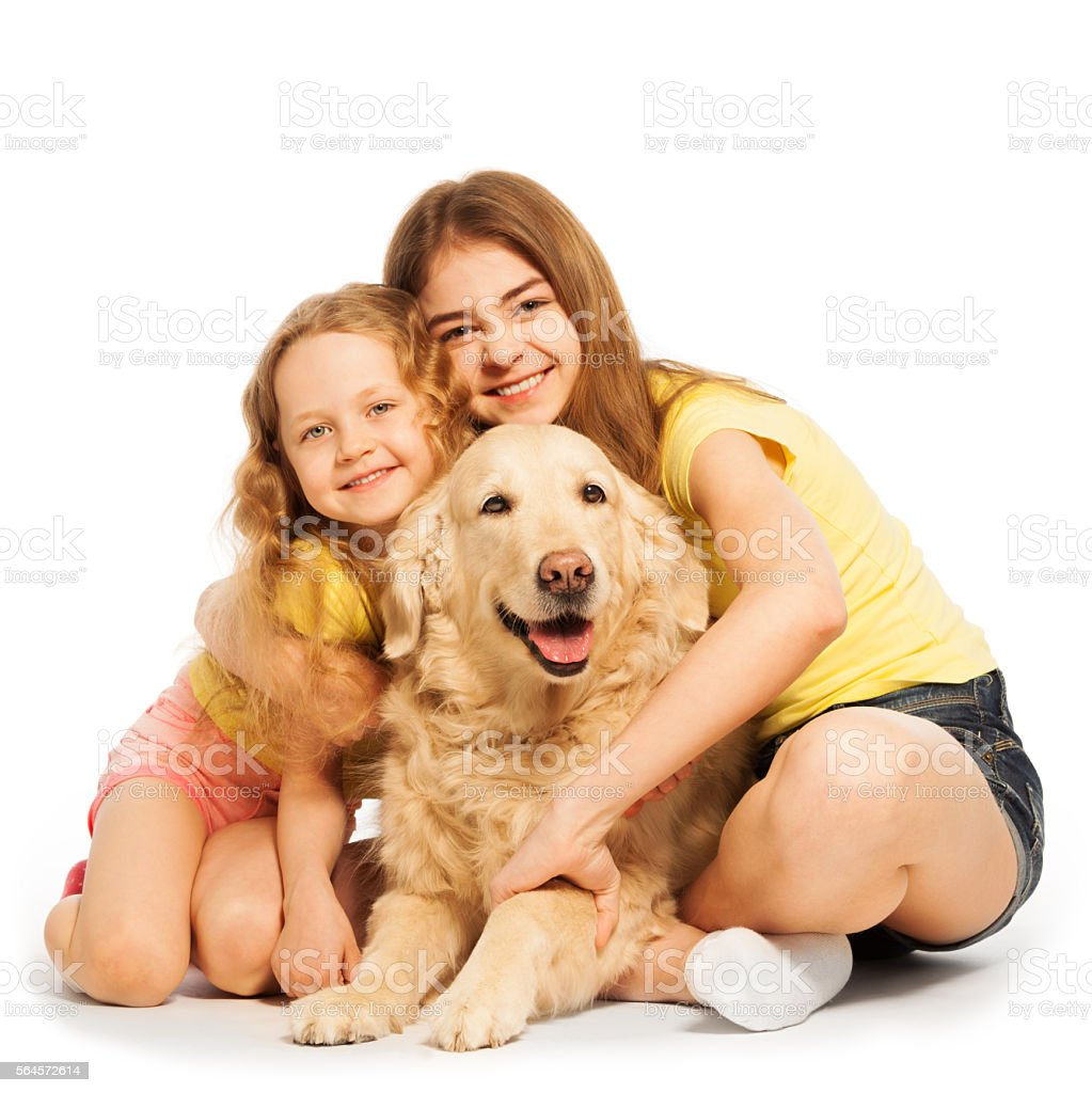 Two happy girls sitting with their pet stock photo