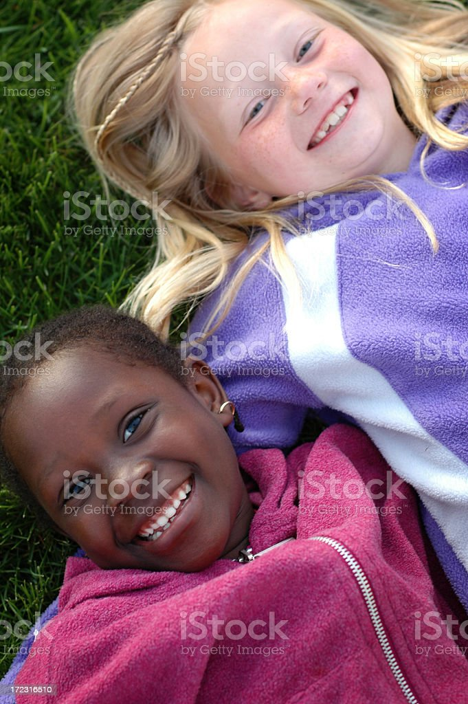 Two Happy Girls Smiling and Lying in the Grass royalty-free stock photo