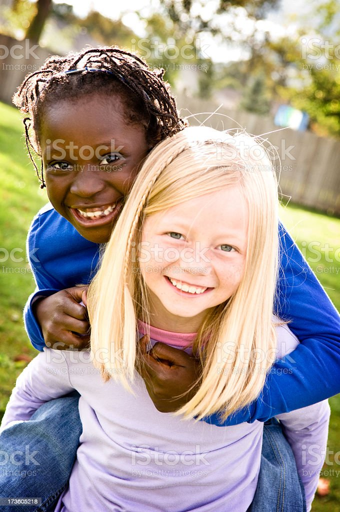 Two Happy Girls Smiling and Riding Piggyback Outside royalty-free stock photo