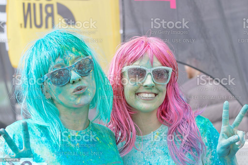 Two happy girls wearing sun glasses covered with color powder stock photo
