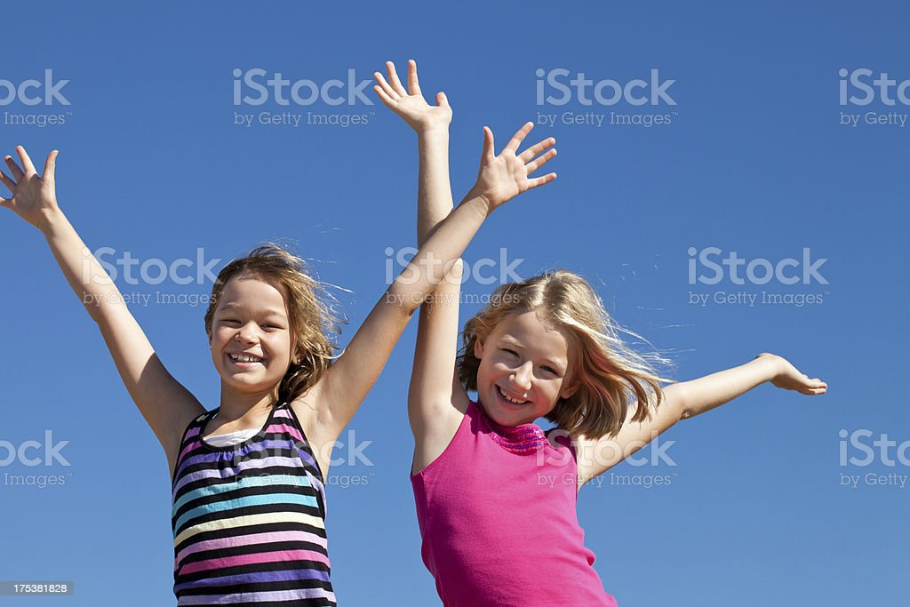 Two happy girls with arms raised up and blue sky royalty-free stock photo