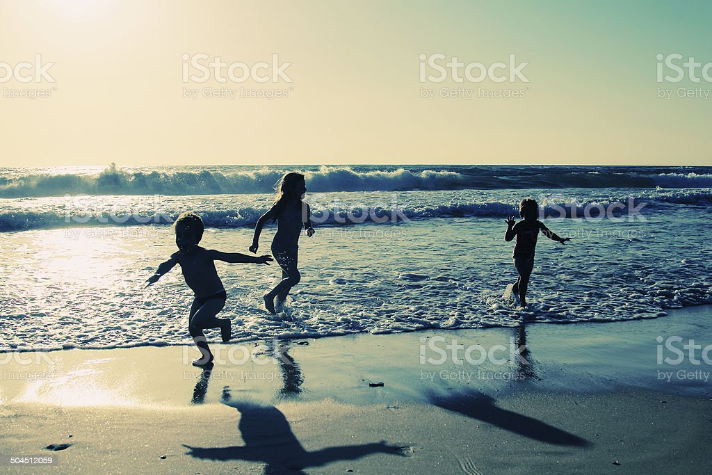two happy kids playing on the beach stock photo