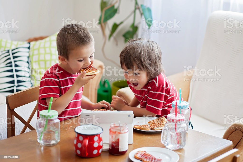 Two happy kids, two brothers, having healthy breakfast sitting a stock photo