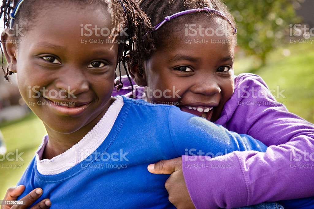 Two Happy Little Girls Smiling and Hugging Outside royalty-free stock photo