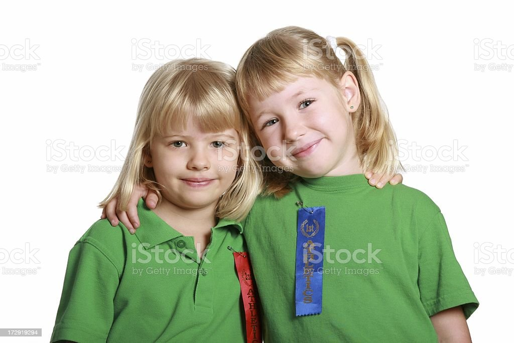 Two happy little girls with sports athletics ribbons on shirts royalty-free stock photo