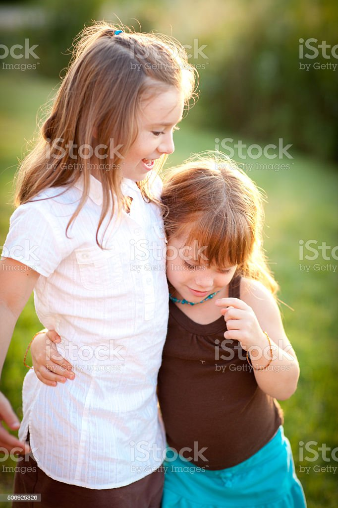 Two Happy Little Sisters Hugging Each Other Outside stock photo